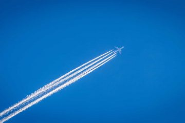 Blue sky with aircraft and its contrails